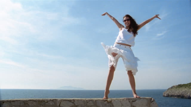 woman posing on ledge overlooking bay with wind blowing skirt / capri - skirt stock videos & royalty-free footage