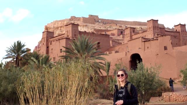 vídeos de stock e filmes b-roll de woman posing to a camera. old walls of ait ben haddou in background - encosta