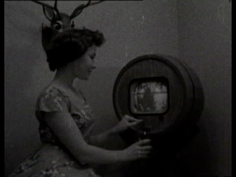 Woman posing with circular television set and television sets in shop window display Early television set on August 27 1958 in London