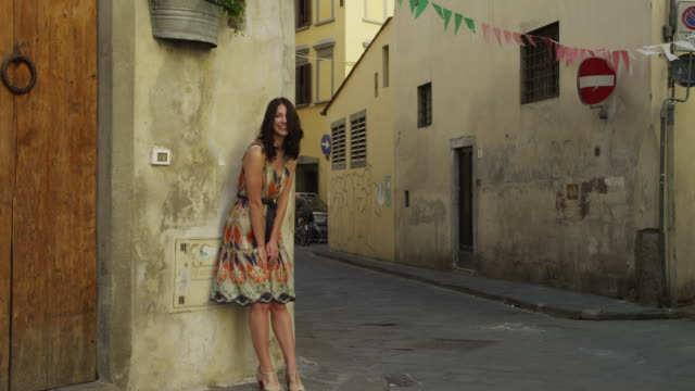 ws woman posing,standing on street corner/ florence,tuscany - 角点の映像素材/bロール