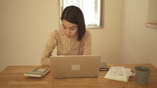 vídeos y material grabado en eventos de stock de una mujer registrando los totales de recibos en una computadora portátil en casa. - una mujer de mediana edad solamente