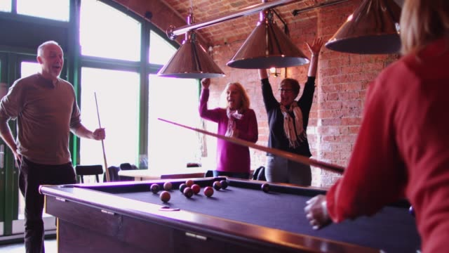 woman potting a pool ball while friends watch - hobbies stock videos & royalty-free footage