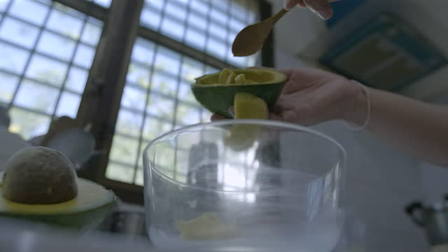woman pouring avocado in bowl slow motion - preparing food stock videos & royalty-free footage