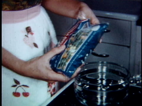 CU PAN Woman pouring bag of frozen vegetables into pot of water / USA