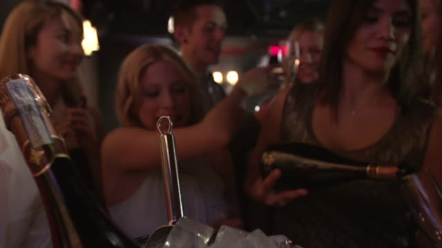 vídeos de stock e filmes b-roll de woman pouring champagne with friends in nightclub lounge - balde de gelo