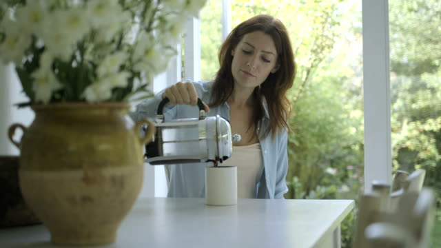 Woman pouring coffee in coffee cup and drinking at dining table.