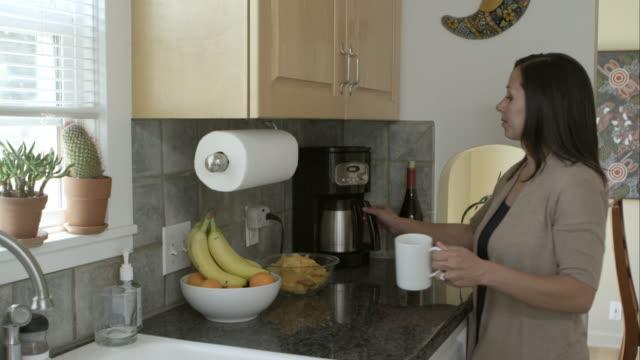 vídeos de stock e filmes b-roll de woman pouring coffee into mug in the kitchen. - só mulheres de idade mediana