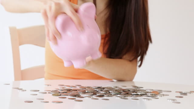 ms tu td woman pouring coins from piggy bank on table / jersey city, new jersey, united states - saving up for a rainy day stock videos and b-roll footage