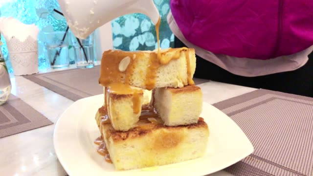 woman pouring dessert topping sweet cream on honey toast bread - dessert topping stock videos & royalty-free footage