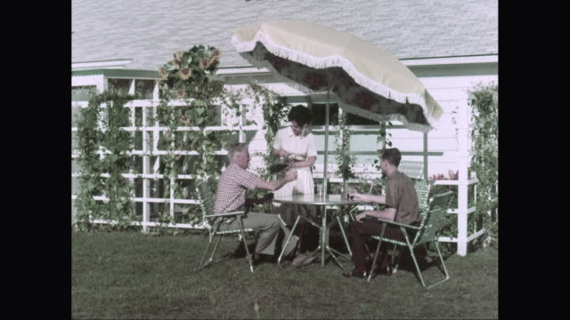ws woman pouring drink to man while sitting in domestic garden / united states - anno 1960 video stock e b–roll