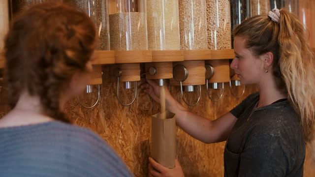 stockvideo's en b-roll-footage met woman pouring grains into paper bag at zero waste store - keus