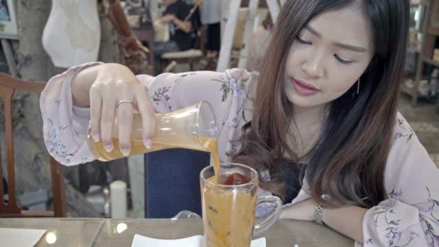 グラスにアイスミルクティーを注ぐ女性 - アイスティー点の映像素材/bロール