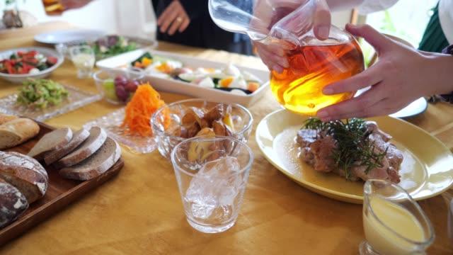 テーブルの上のグラスに氷茶を注ぐ女性 - アイスティー点の映像素材/bロール