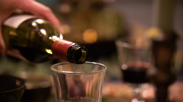 woman pouring red wine into a wine glass on a christmas decorated table setting. 4k slow-motion - グラス点の映像素材/bロール