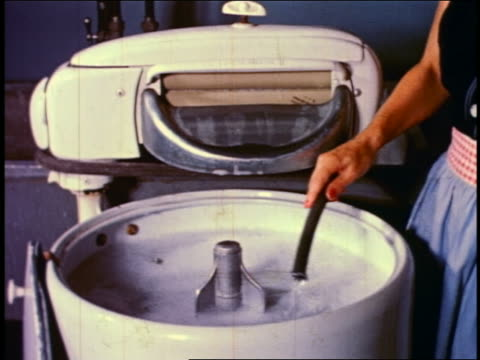 1950 woman pouring soap into + operating old-fashioned electric washing machine - 1950点の映像素材/bロール