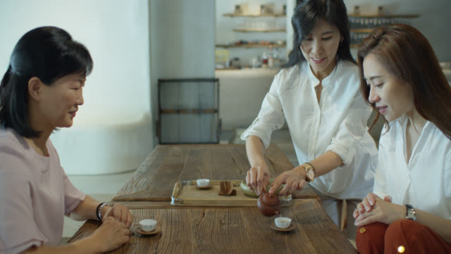 woman pouring tea for her friends - cup stock videos & royalty-free footage
