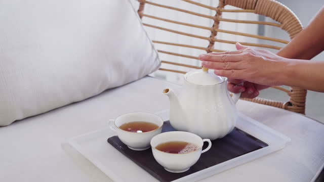 woman pouring tea from teapot into cup on sofa at home, tea ceremony concept - saucer stock videos & royalty-free footage