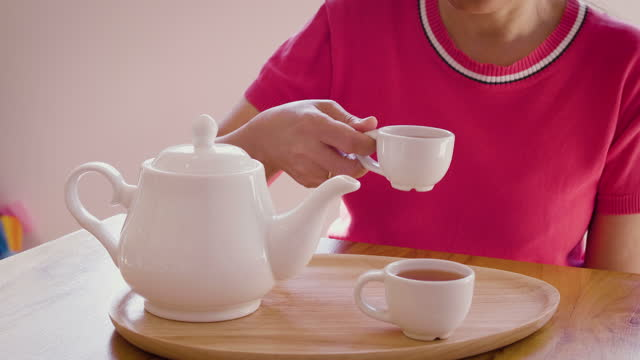woman pouring tea from teapot into cup on wooden table at home, tea ceremony concept - saucer stock videos & royalty-free footage
