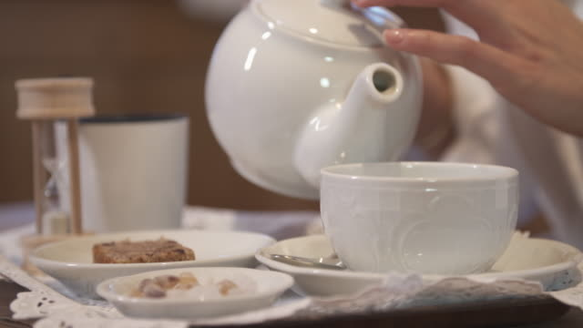 a woman pouring tea in a hotel room at a ski resort. - teapot stock videos & royalty-free footage