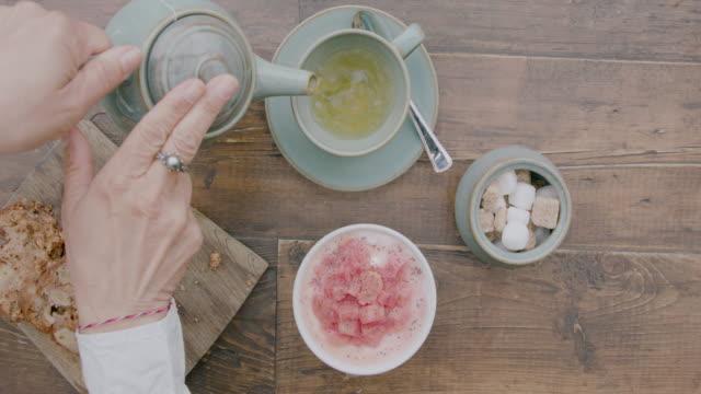 vídeos de stock e filmes b-roll de woman pouring tea - chipping norton england