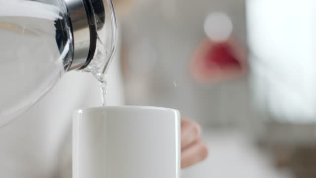woman pouring water in mug - boiling stock videos & royalty-free footage