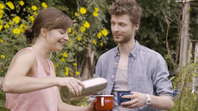 woman pours coffee from flasks in cups, sitting with boyfriend in community garden - 分かち合い点の映像素材/bロール