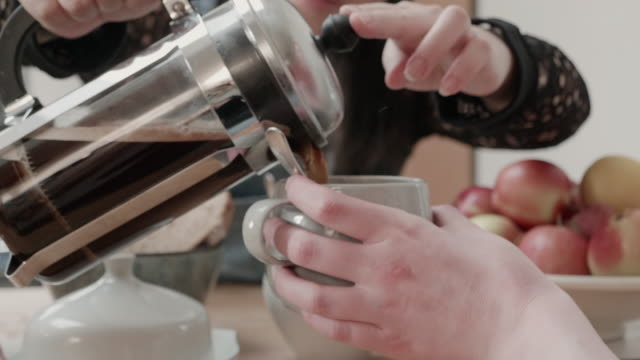 woman pours coffee using cafetiere into friends mug, friend passes milk jug. - milk jug stock videos & royalty-free footage