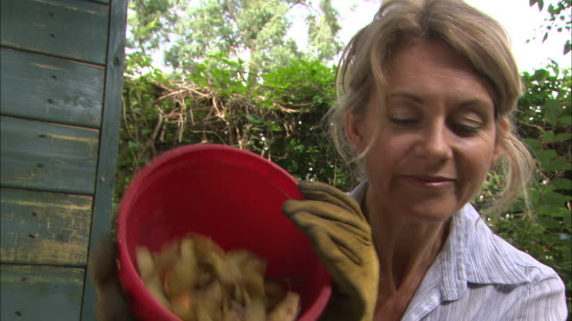 la woman pours compost onto heap - gardening glove stock videos & royalty-free footage