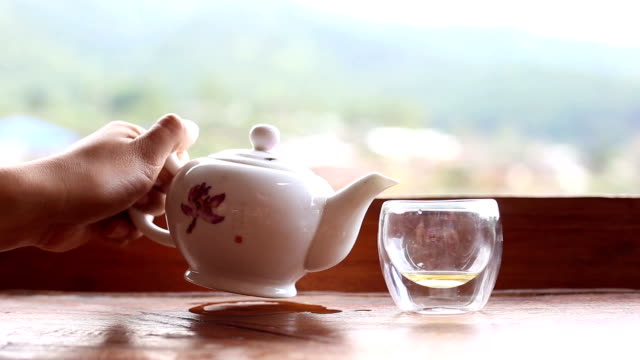 woman pours green tea to tea cup - teapot stock videos & royalty-free footage