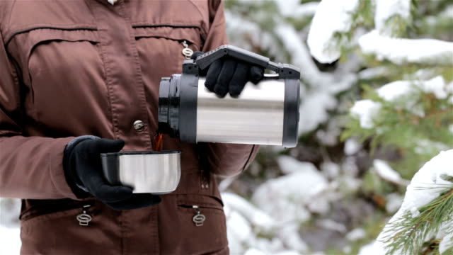 Woman pours hot tea from a thermos into a cup.