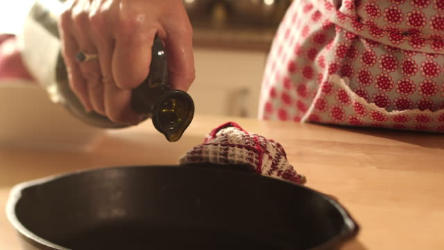 a woman pours oil in the pan in cast iron - cast iron stock videos & royalty-free footage