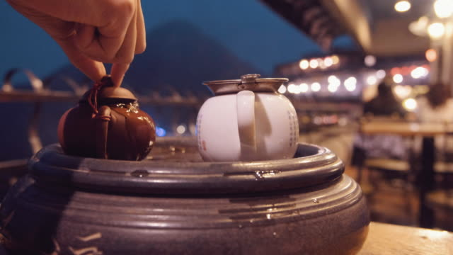 a woman pours tea in jiufen taipei taiwan at night - tea pot stock videos and b-roll footage