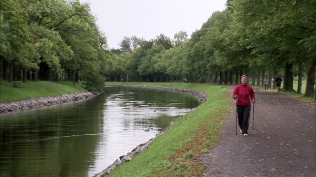 woman power walking alongside a canal, sweden. - power walking stock videos and b-roll footage