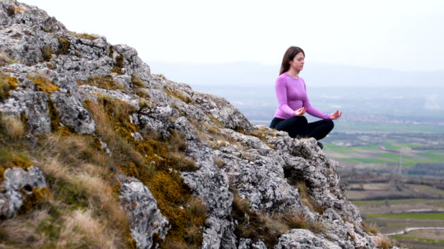 Woman practice yoga at the mountain