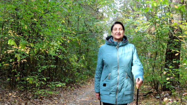 a woman practices nordic walking in the forest. - condition stock videos & royalty-free footage
