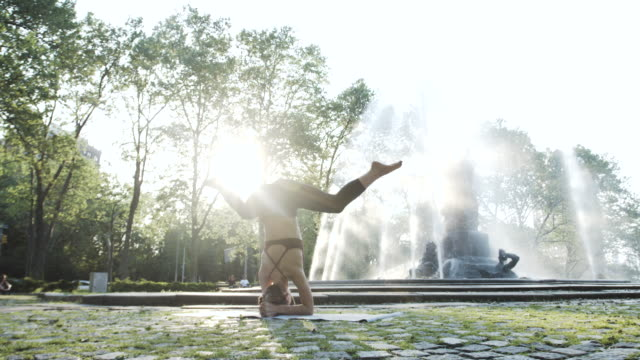 A woman practices Yoga, alone, outdoors on an early morning - 4k - slow motion