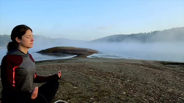 woman practices yoga and meditates in the lotus position - harmony stock videos & royalty-free footage
