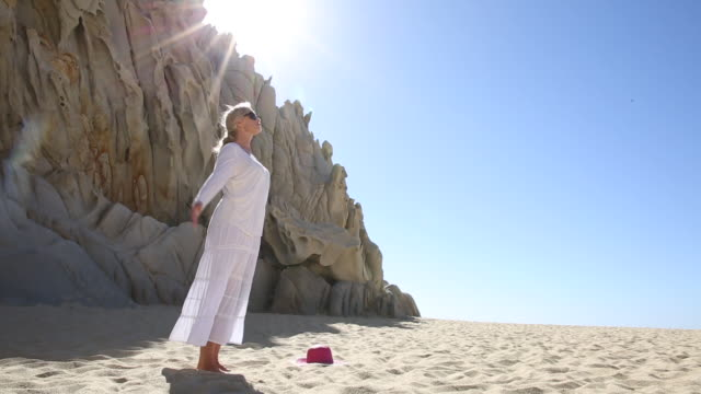 Woman practices yoga moves on beach, below cliffs