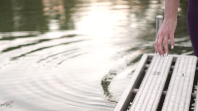 woman practices yoga on a dock - リフレクション湖点の映像素材/bロール