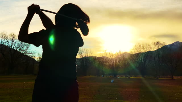 woman practicing golf swing on driving range in sunset - golf swing from behind stock videos & royalty-free footage