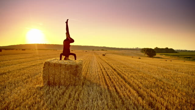 DS Woman practicing headstand position on a bale at sunset