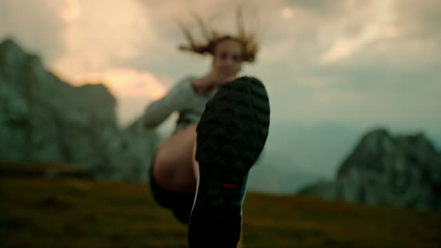 slo mo woman practicing martial arts kicks in mountains - persistence stock videos & royalty-free footage