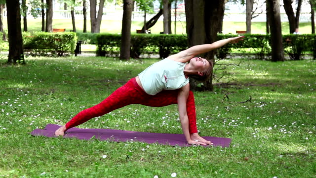 woman practicing outdoor yoga in the park - thin stock videos & royalty-free footage
