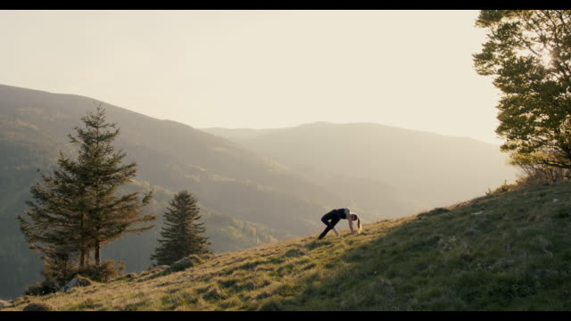 woman practicing yoga against spectacular scenery - vor stock-videos und b-roll-filmmaterial