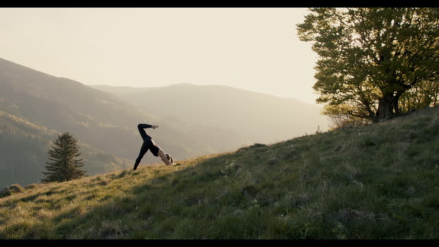 woman practicing yoga against spectacular scenery - relaxation stock-videos und b-roll-filmmaterial