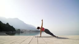 woman practicing yoga asanas on seaside boardwalk with mountains on background