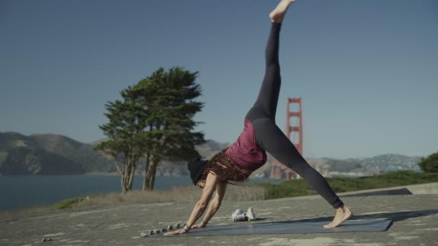 stockvideo's en b-roll-footage met woman practicing yoga at windy waterfront / san francisco, california, united states - benen gespreid