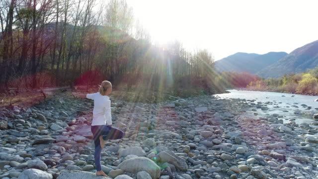 vídeos de stock, filmes e b-roll de mulher praticando ioga pelo rio, tiro do zangão - pose de arvore