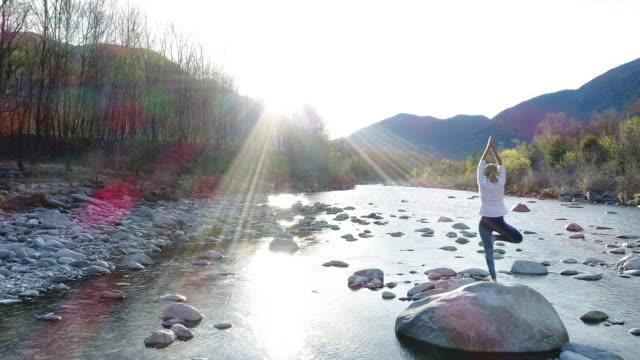 vídeos y material grabado en eventos de stock de mujer practicando yoga junto al río, tiro del zumbido - vriksha asana