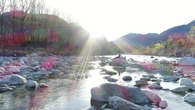 vidéos et rushes de femme pratique l'yoga de la rivière, tir de drone - seulement des jeunes femmes